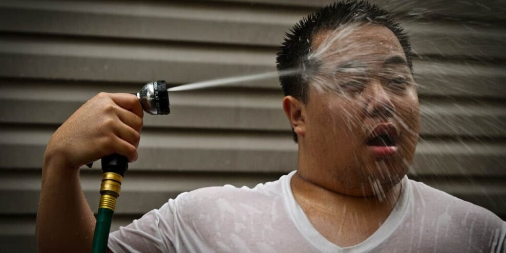 A man seeks relief during a heat wave with a garden hose shower.