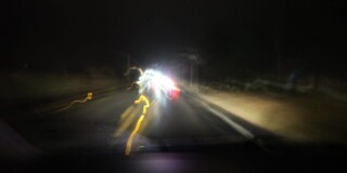 Streaky lights from a car swerve around the road at night.