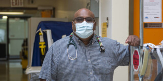 Dr. Prean Armogam leans on some medical equipment. He is wearing a mask and has a stethoscope hung around his neck.