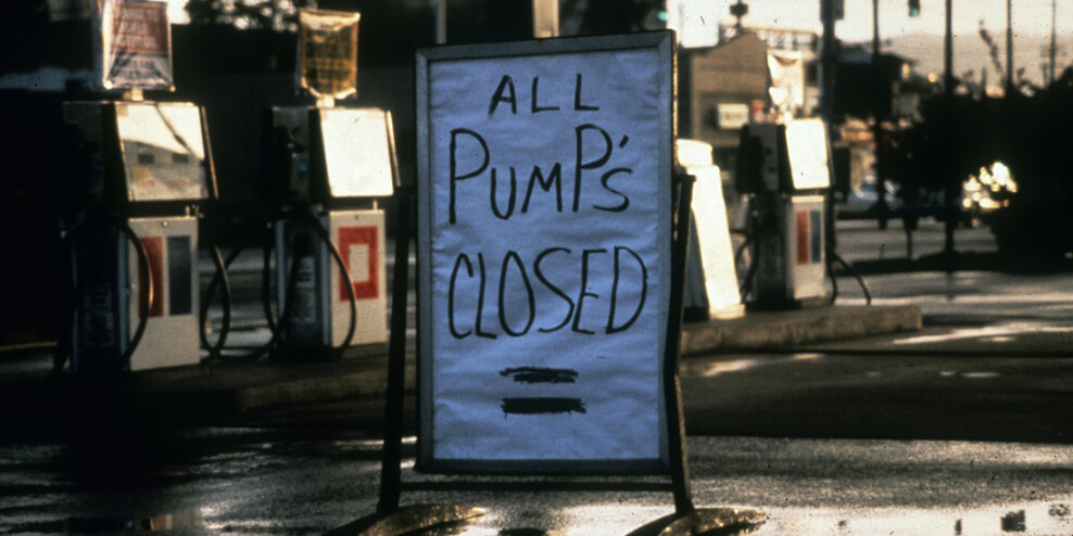 """A handmade sign out front of a gas station that reads """"All pumps closed""""."""
