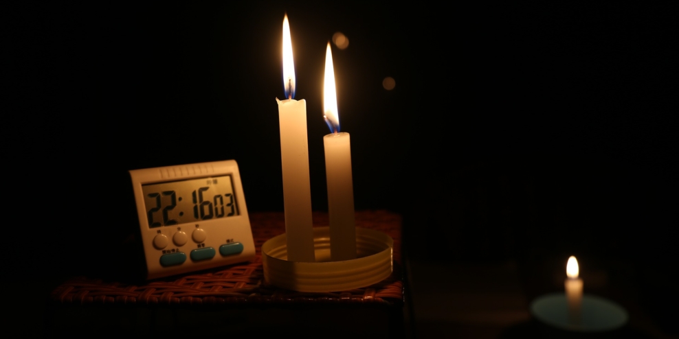 Candles illuminate a small digital clock that reads 10:16pm.