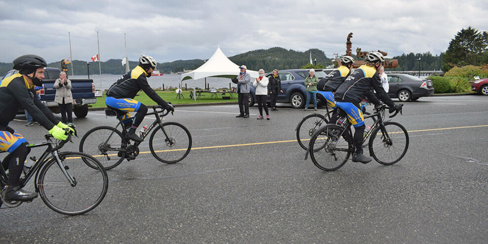 Cyclists ride off while people wave on a cloudy day.